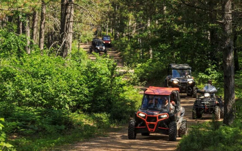 Off-road utility vehicles riding on a dirt path.