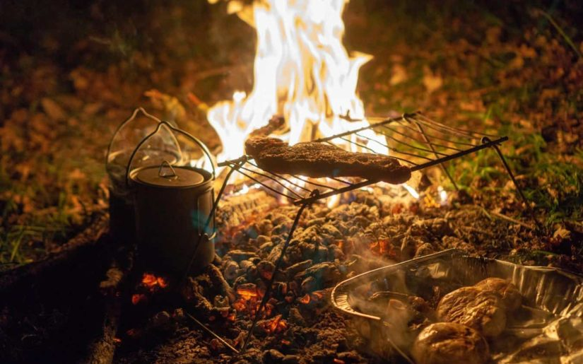 Meat cooking over a campfire
