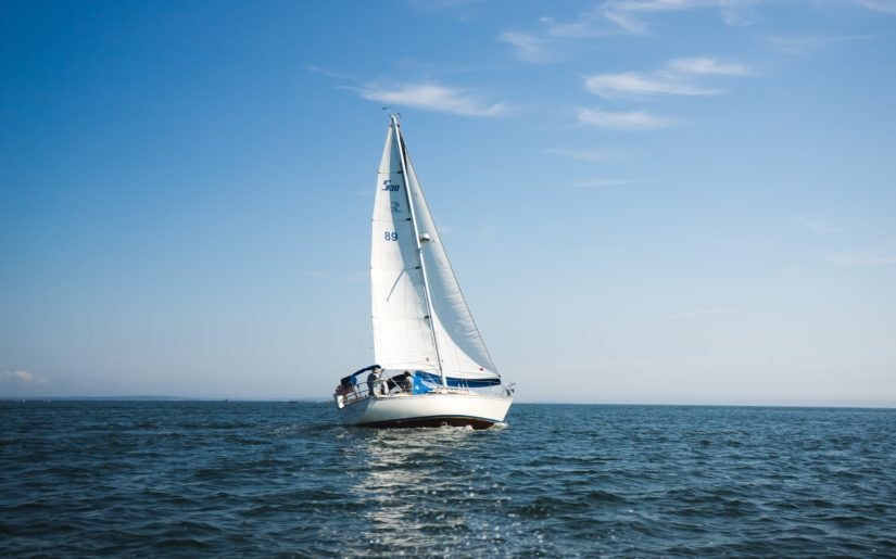 Sail boat sailing on the open waters under a blue sky.