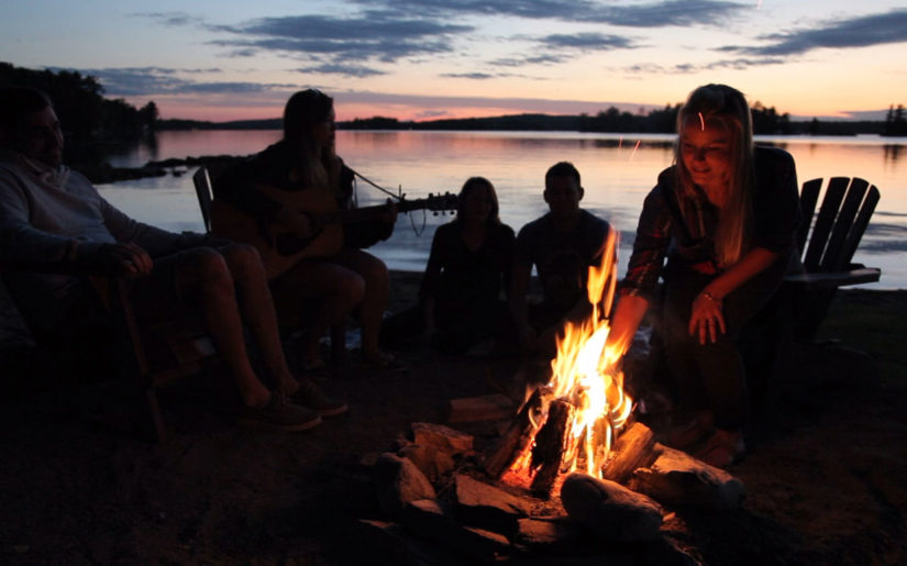 Cottagers sitting around campfire, singing songs.