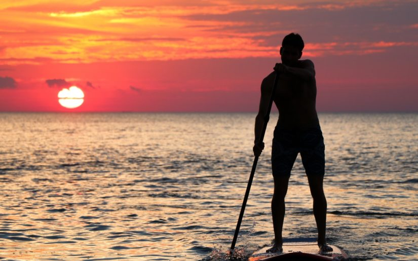 Silhouette of male stand-up paddleboarder at sunset.