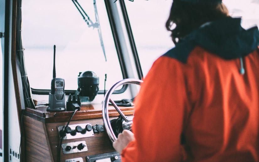 Captain wearing an orange rain jacket, navigating the waters on the bridge of a vessel.