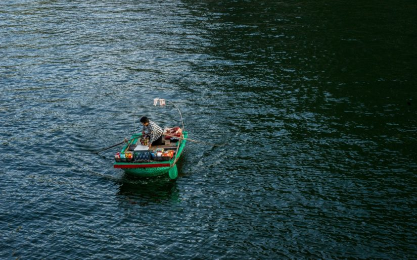 Woman stnading up in a small row boat.