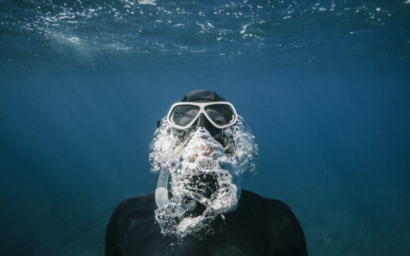 Snorkeler wearing mask and snorkel, exhaling while swimming to the surface.