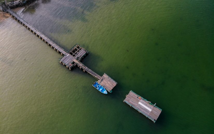 Aerial view of small motorboat properly tied to a dock.