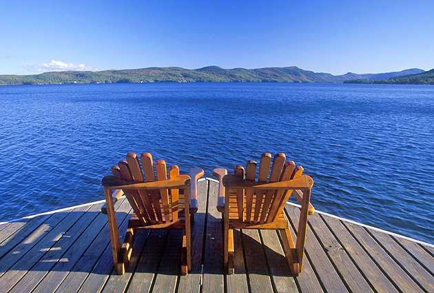 Two adirondack chairs on a dock overlooking New York lake.