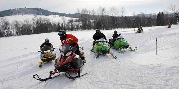 Six snowmobilers on a trail in New York.