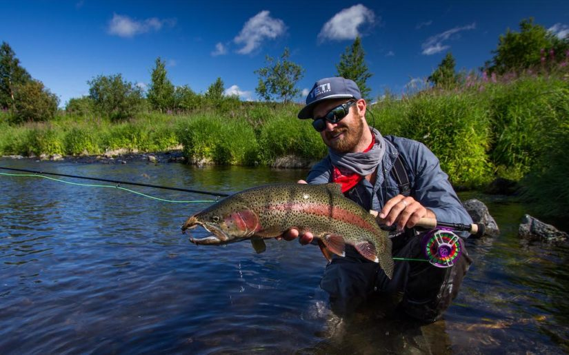 Campfire Collective Ambassador Christiaan Pretorius holding up rainbow trout caught with mouse.