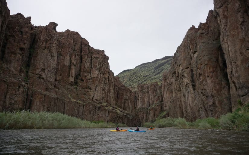Three kayakers resting on the water below a Ecuador gorge.